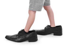 Boy`s little feet in big black style shoes